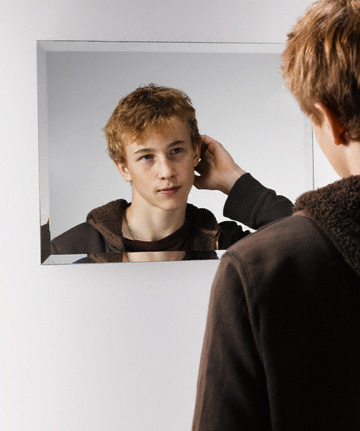 Teenage Boy Looking at Himself in a Mirror --- Image by © Corbis